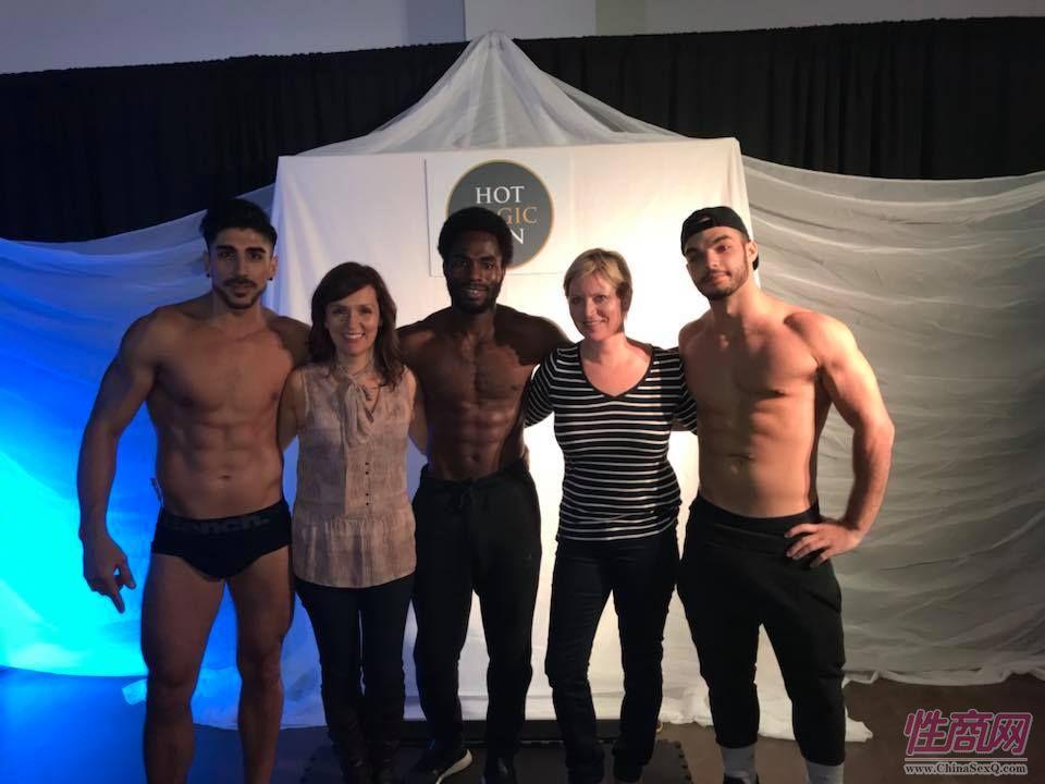 两位中年女观众与肌肉男模特合影