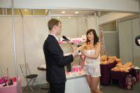 性玩具展商向美女记者介绍新款玩具