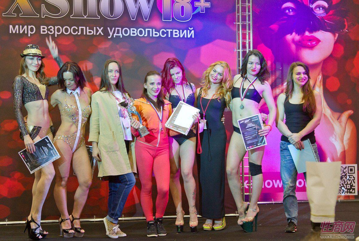 获奖模特手持俄罗斯成人展组委会颁发的获奖证书在舞台上合影