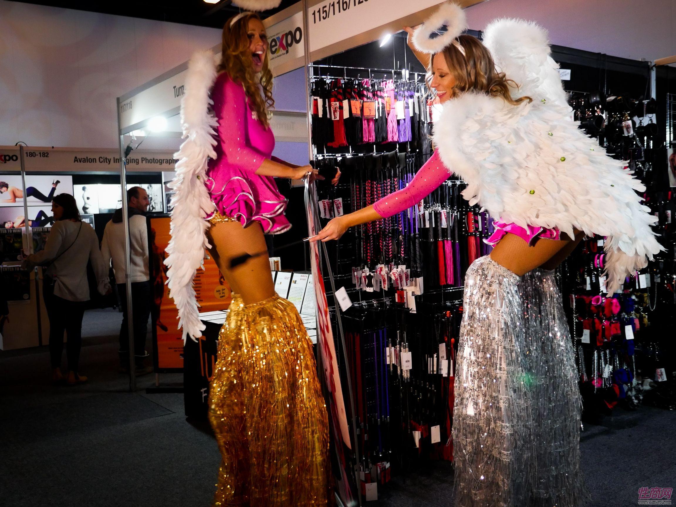 两位女模特踩着高跷在展馆里穿梭